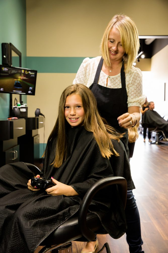 Picture of a girl sitting in a salon chair having her hair styled by a professional Stylist.  The girl is smiling and seems to be enjoying her hair cutting experience.  The kids area at Just Cut It is designed for kids to have a great hair cutting experience.  It features video game stations and coloring tables to keep kids busy during their wait and Just Cut It.